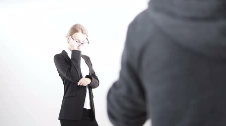 Photographer is shooting an intelligent dark hair caucasian businesswoman, in a white blouse and a black suit, putting on her glasses, in the white background, isolated, slow motion Vídeos