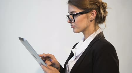 Occupied young dark hair caucasian businesswoman, in a white blouse and a black jacket, is using her tablet in the white background, isolated, slow motion
