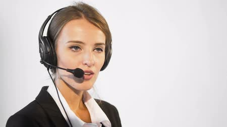 Attractive young dark hair caucasian callcenter operator, in a white blouse and a black jacket, is talking on the headset, in the white background, isolated, slow motion