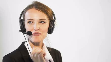 Smiling young dark hair caucasian callcenter operator, in a white blouse and a black jacket, is talking on the headset, in the white background, isolated, slow motion