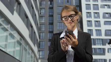 Self-confident young dark hair caucasian businesswoman, in a white blouse and a black jacket, is texting a message on the phone in front of the modern corporation building in the background, slow motion Vídeos