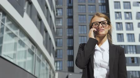 Happy young dark hair caucasian businesswoman, in a white blouse and a black jacket, is talking on the phone while walking in front of the modern corporation building in the background, slow motion