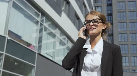 Joyful young dark hair caucasian businesswoman, in a white blouse and a black jacket, is talking on the phone in front of the modern corporation building in the background, slow motion Vídeos