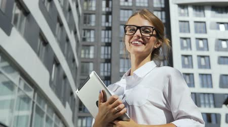 Smiling and self-confident young dark hair caucasian businesswoman, in a white blouse and stylish glasses, is holding her tablet and standing in front of the modern corporation building in the background, slow motion