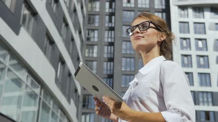 Smiling and self-confident young dark hair caucasian businesswoman, in a white blouse and stylish glasses, is using her tablet in front of the modern corporation building in the background, slow motion