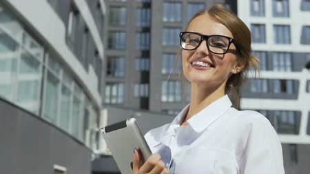 Happy and self-confident young dark hair caucasian businesswoman, in a white blouse and stylish glasses, is holding the tablet in front of the modern corporation building in the background, slow motion 影像素材
