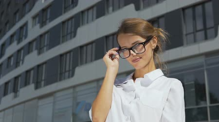 Intelligent and self-confident young dark hair caucasian businesswoman, in a white blouse, is putting on her stylish glasses in front of the modern corporation building in the background, slow motion