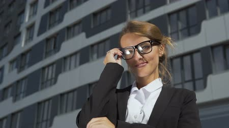Intelligent and self-confident young dark hair caucasian businesswoman, in a white blouse and a black jacket, is putting on her stylish glasses in front of the modern corporation building in the background, slow motion Vídeos