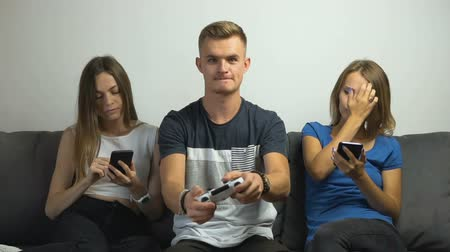 банда : Cute caucasian teen girls got tired of gripped teen boy playing a video game on the comfortabe sofa, slow motion