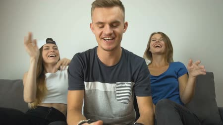 банда : Cute caucasian teenagers have fun, playing video games on the comfortabe sofa, slow motion