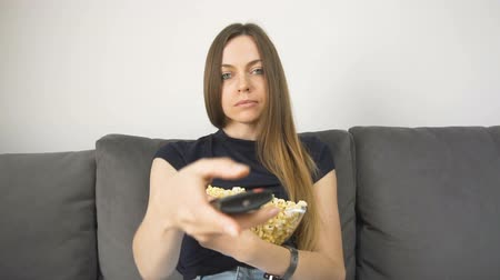 Relaxed and cute girl watches television, eating popcorn on the comfortable grey sofa, slow motion