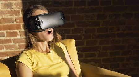 bilinmeyen : Pretty caucasian girl uses a virtual reality helm in her yellow armchair, excitement of a new experience, slow motion