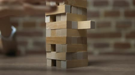 logic : Block game, caucasian girl moving a block out of the tower on table near brick wall, close-up, slow motion