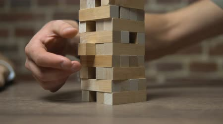 lógica : Block game, caucasian boy pushing a block out of the tower on table near brick wall, close-up, slow motion