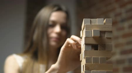 logic : Block game, caucasian dark hair girl takes turn to push the block out of the tower, near the brick wall, slow motion