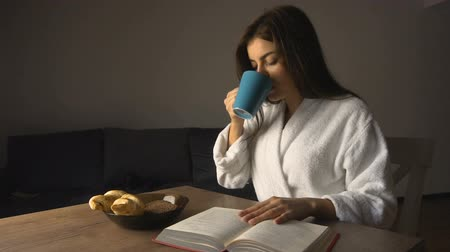 Pretty caucasian long hair girl, in a white bathrobe, reading a book while having coffee in the kitchen, slow motion