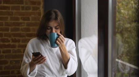 descontraído : Beautiful long hair caucasian woman, in white bathrobe, using her phone while having coffee and looking out of the window, morning time, slow motion