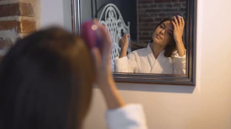 skin brown : Beautiful caucasian girl brushing her dark long straight hair in front of the mirror, slow motion Stock Footage