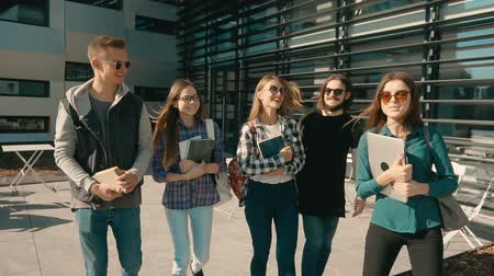 integrovaný : Group of young attractive students walk before modern building, have a pleasant talk, cafe sunny day steady 120FPS slowmotion
