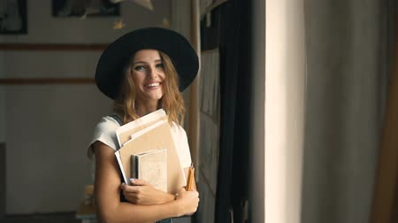 plavé vlasy : Beautiful long hair female artist, in a black hat and denim dress, holding her sketches and pencils near the studio window, slow indoor motion