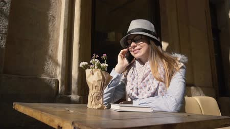 bescheiden : Caucasian girl, in grey striped hat and coloured scarf, chatting on the phone in outdoor cafe, slowmotion on sunny autumn day
