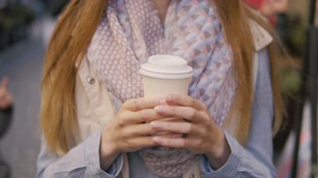 szerény : Caucasian girl, in striped shirt and coloured scarf, holding coffee in the street, close-up slowmotion of hands Stock mozgókép