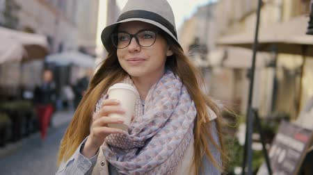 bescheiden : Relaxed caucasian girl, in striped hat and coloured scarf, having coffee while walking in the street, sunny day, slowmotion