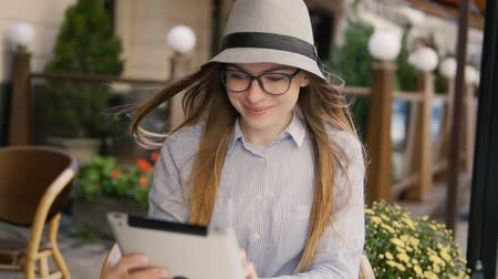 szerény : Intelligent caucasian girl, in a grey striped hat, using silver tablet with pleasure in a cafe, outdoor slowmotion