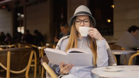 bescheiden : Beautiful caucasian girl, in a grey striped hat and glasses, reading a book during coffee time in the outdoor cafe, slowmotion Stockvideo