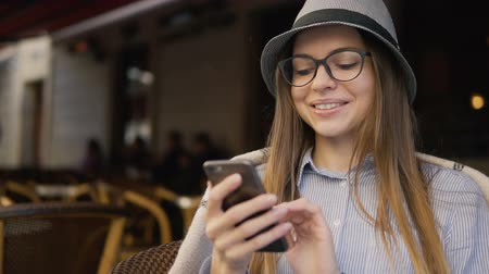 szerény : Portrait of caucasian girl in a grey striped hat texting on mobile phone in the outside cafe, slowmotion