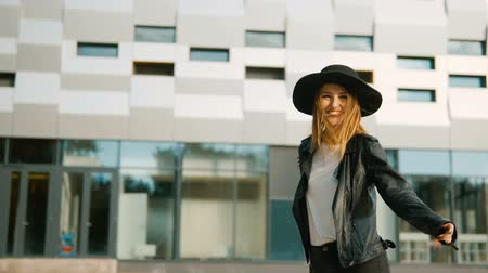 carelessness : Fashionable caucasian girl, in black hat, turning around happily before modern building , slowmotion