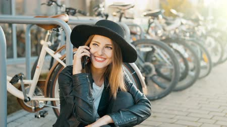 targi : Happy caucasian girl, in black hat and leather jacket, talking on the phone before bikes, outdoor slowmotion in sunset time