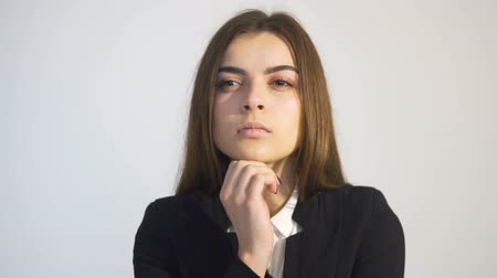 ambition : Serious businesswoman, in white blouse and black jacket, looking forward while thinking, isolated slowmotion in white background Stock Footage
