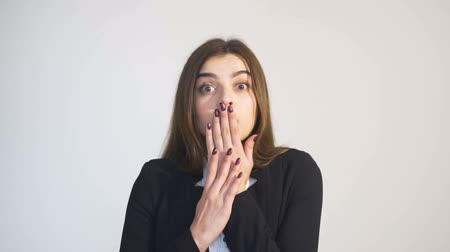 sudden : Portrait of scared woman, in white blouse and black jacket, covering mouth with hands, isolated slowmotion Stock Footage