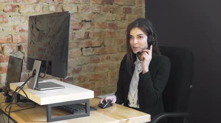 assistência : Callcenter operator, in white blouse and black jacket, talking on the headset at the desk in office, slowmotion Vídeos