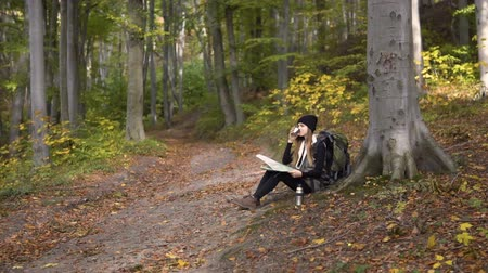 trousers : Smiling long hair girl, with green backpack, having tea and looking at the map while resting in the wood, slowmotion