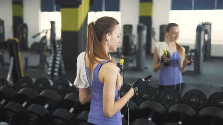 vest : Smiling and fit caucasian girl with sportsbottle in left hand using mobile phone before the mirror at the gym, slowmotion Stock Footage