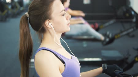 puxar : Pretty girl, in purple vest and white headphones, doing rowing workout at the gym