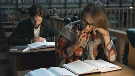 杭 : Two persistent students, man and girl, are studying with books in library reading hall in evening time