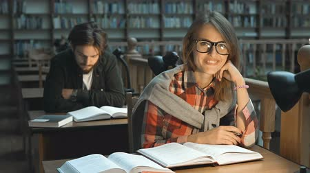 одноклассник : Persistent student girl preparing to exam in library reading hall in evening time Стоковые видеозаписи