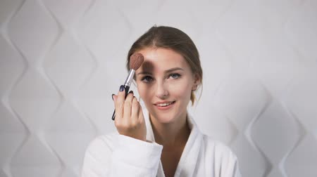 corar : Lovely girl in the white bathrobe using makeup brush in the white background Stock Footage