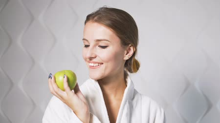 eszik : Happy woman in the white bathrobe showing a green apple, indoor shot in the white background