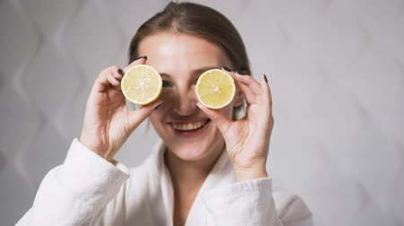 cytryna : Lovely, smiling girl having fun with two halves of lemon, indoor shot in the white background