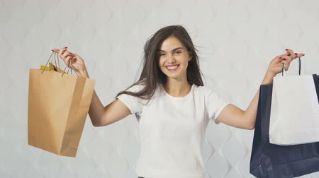 alku : Pretty caucasian girl in white t-shirt showing the shopping bags happily, indoor isolated shot in the white background