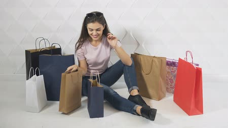 barganha : Beautiful brunet looks into shopping bags and enjoys purchases, isolated indoor shot