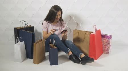 conveniente : Cheerful brunet, surrounded by shopping bags, making online payment on smartphone in the white background