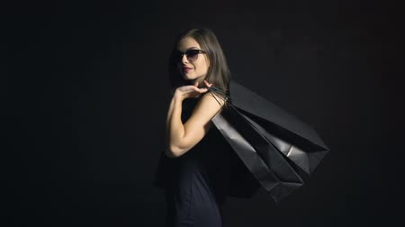 vissza : Back view of sexy girl, in elegant black dress, carrying shopping bags on black friday, indoor shot in the black background Stock mozgókép