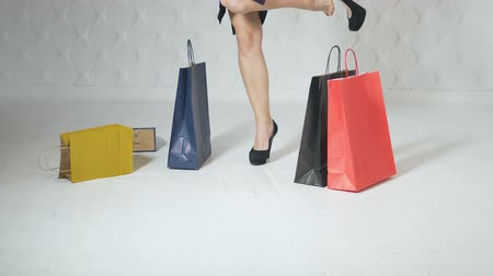 pedikür : Slim and elegant girl, in smart black clothes, drops shopping bags and takes off high-heeled shoes, indoor low shot