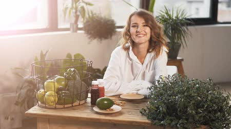 brócolis : Fair-haired girl sitting down at the table full of healthy food, indoor shot among green plants Stock Footage