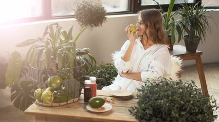 színésznő : Fair-haired girl smelling a green apple with pleasure at the table full of healthy food, indoor shot among green plants